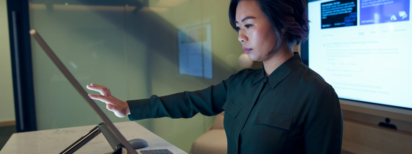 Side profile of a woman wearing a dark shirt in a dim office scrolling or working on a Microsoft Surface Studio.