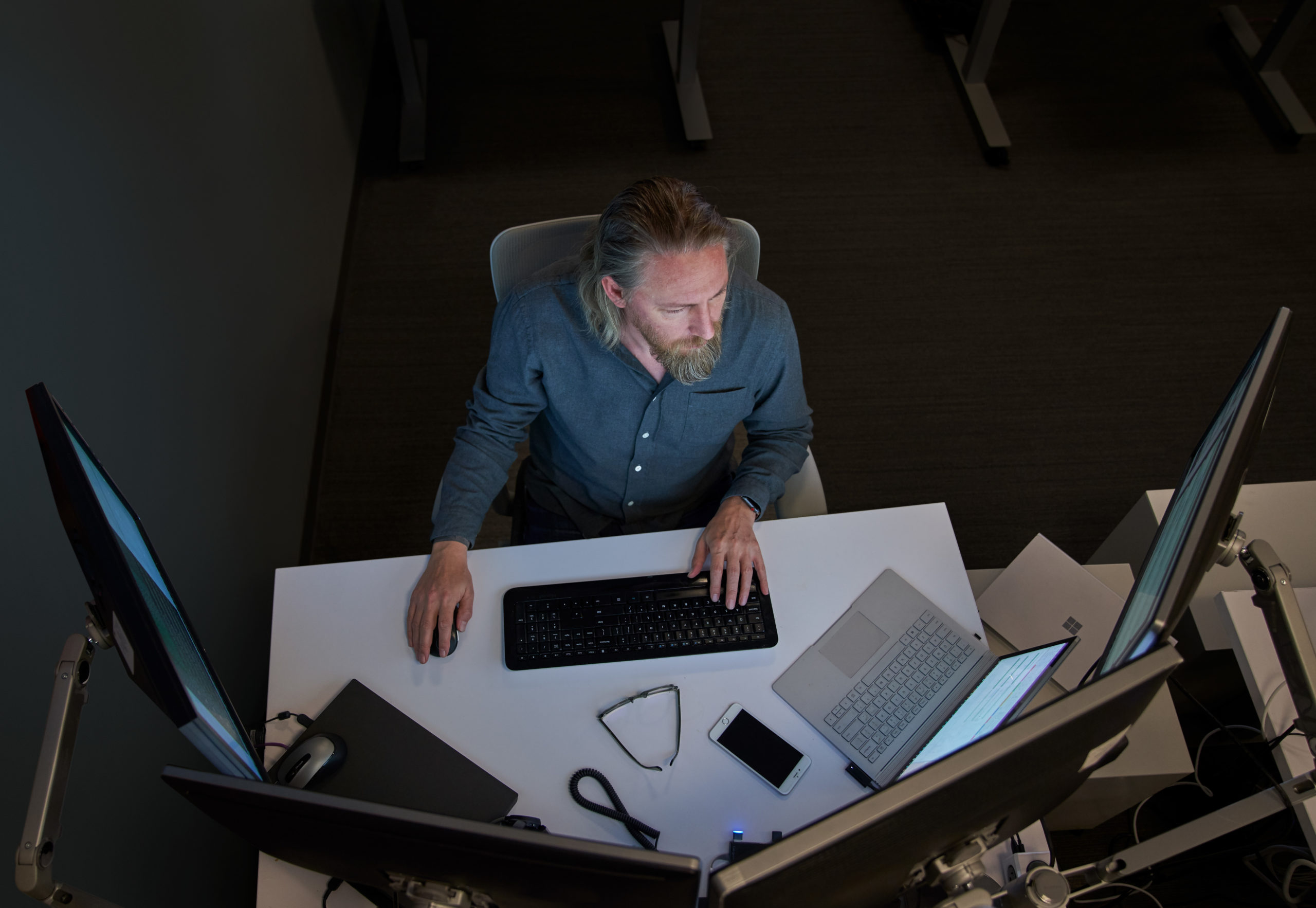 Top-down view of a bearded man in a gray/blue shirt seated at a desk working on a Surface laptop connected to three large monitors.