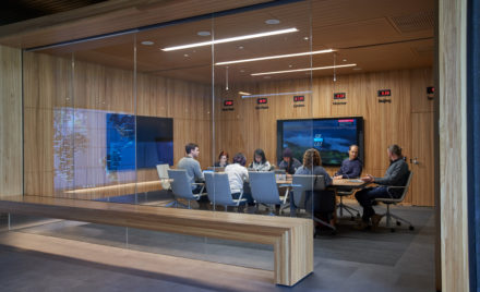 Conference room or board room meeting with people sitting around table in a room with international time clocks, and a map projection/reflection.