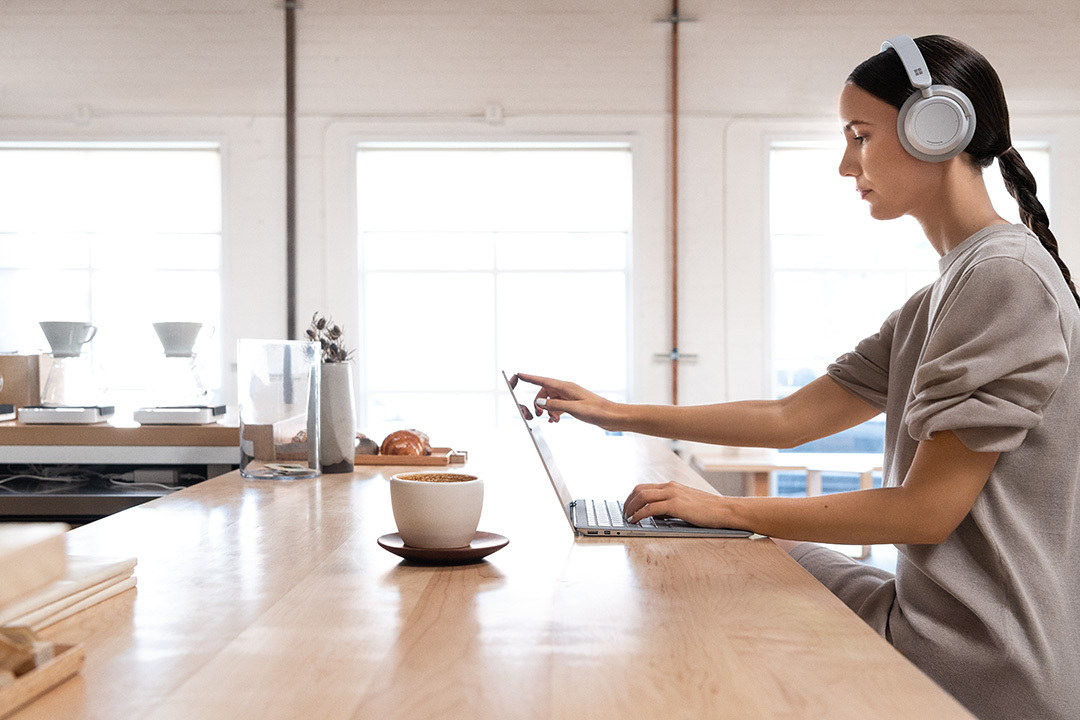 Contextual image of woman wearing Surface headphones working on Surface Laptop2 inside