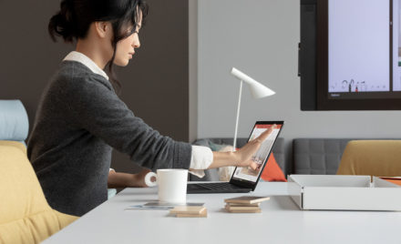 Contextual image of woman touching screen while working on Black Surface Laptop2 inside at desk