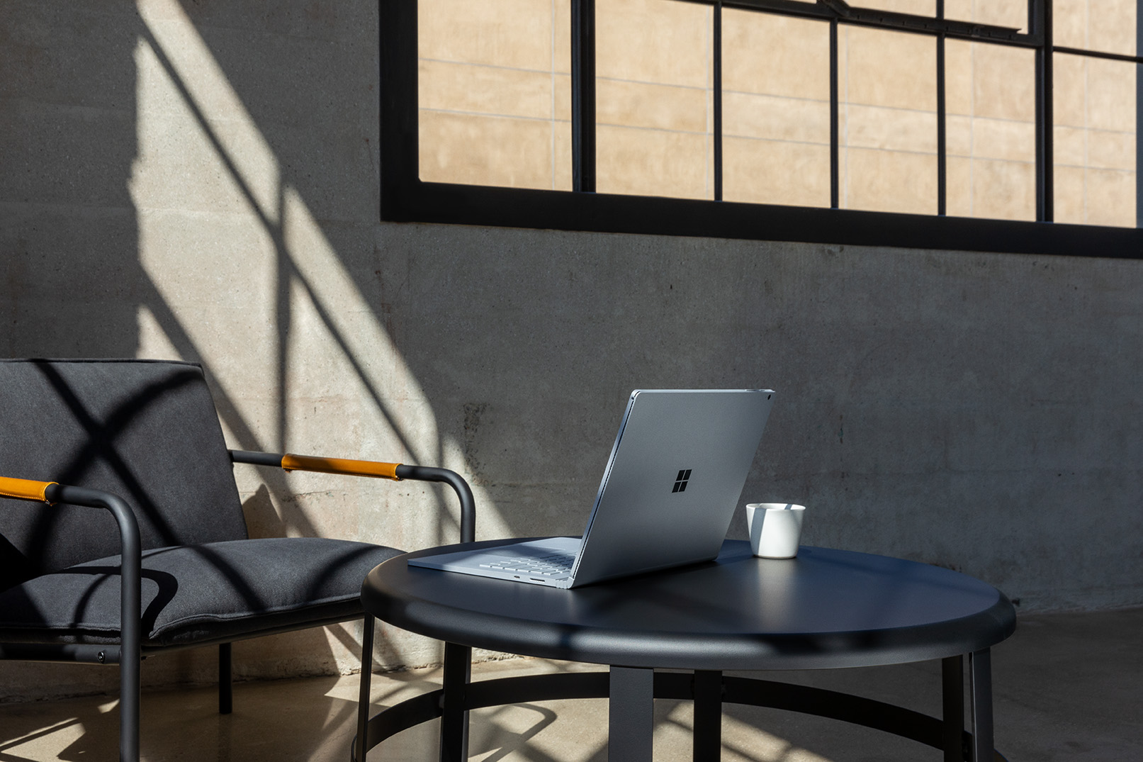 Commercial contextual lifestyle image of Surface Book 3 at desk in office alone.