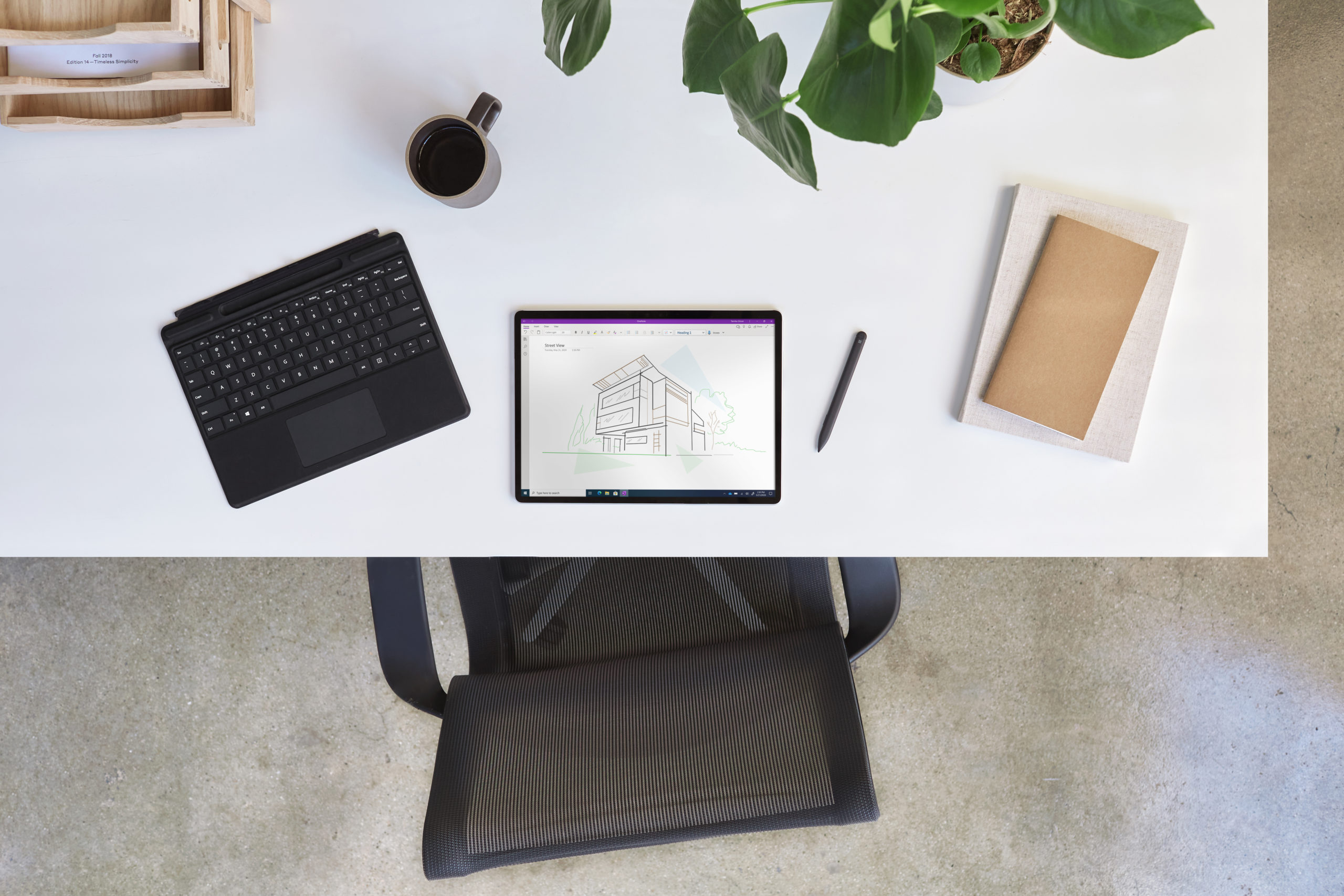 Bird's eye view of Surface Pro X projecting OneNote with a detached black keyboard, pen, books, plant, mug, and wooden shelf.