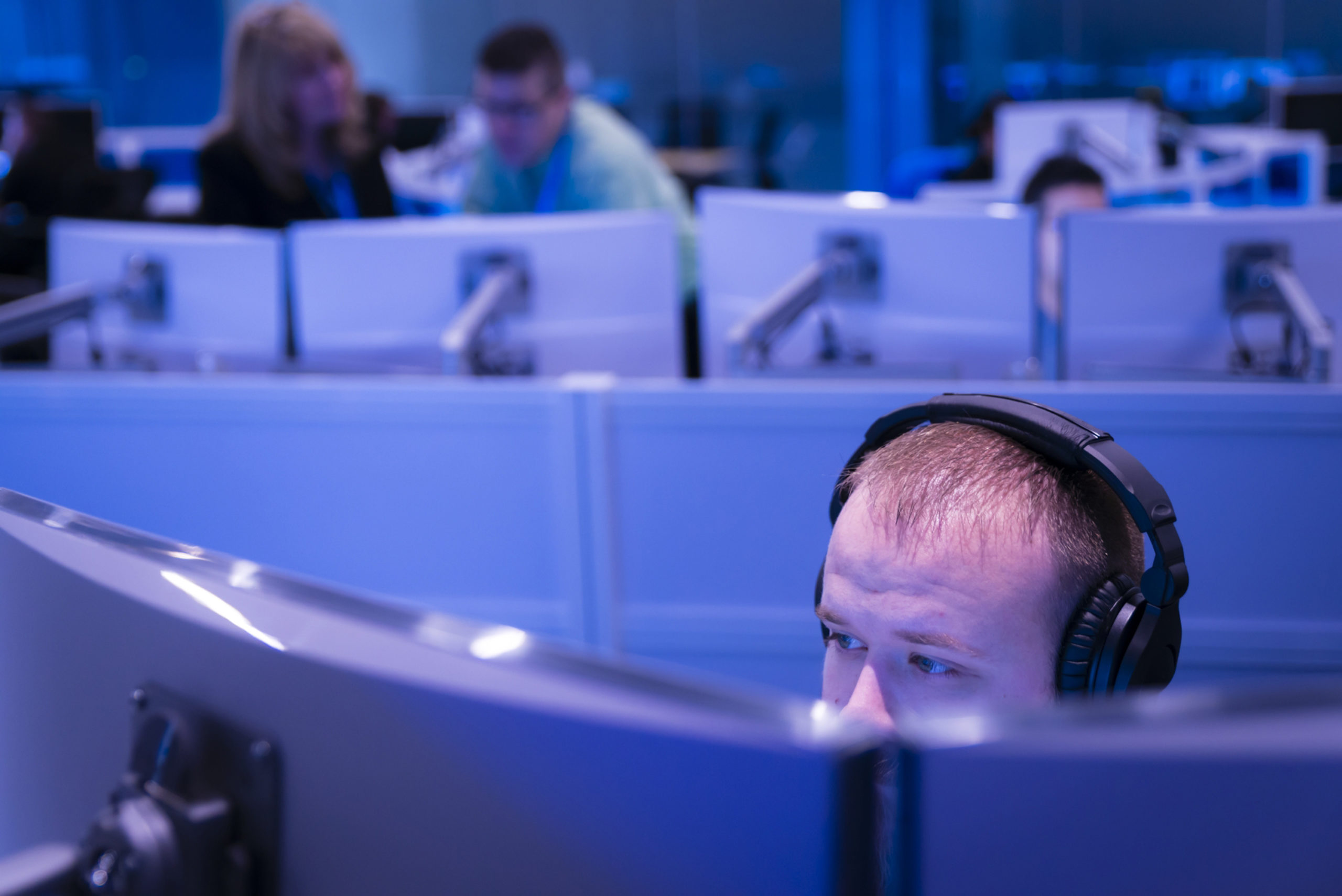 Man working while wearing headphones in the Microsoft Cyber Defense Operations Center
