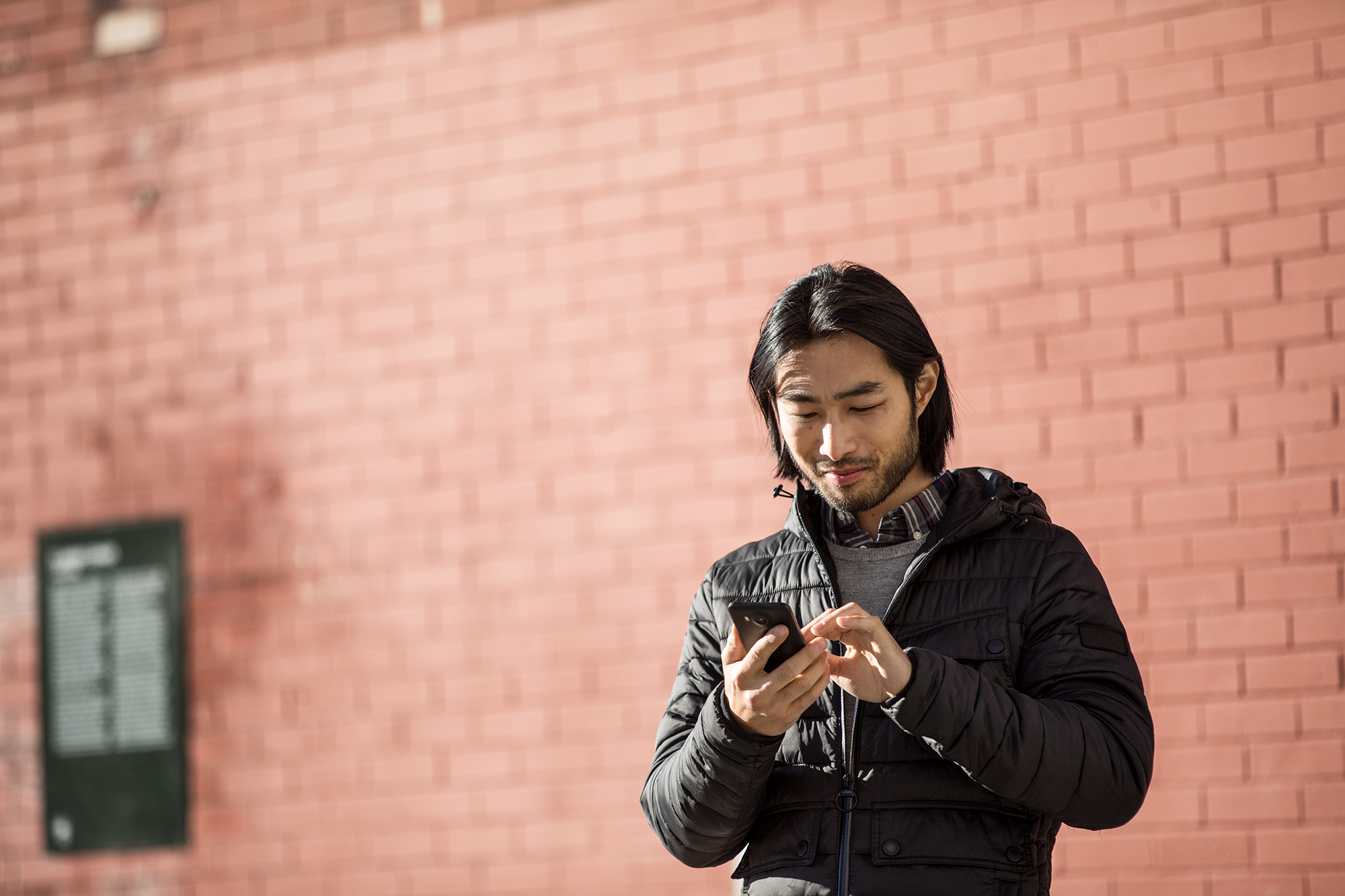 Man holding and interacting with cell phone in front of brick wall