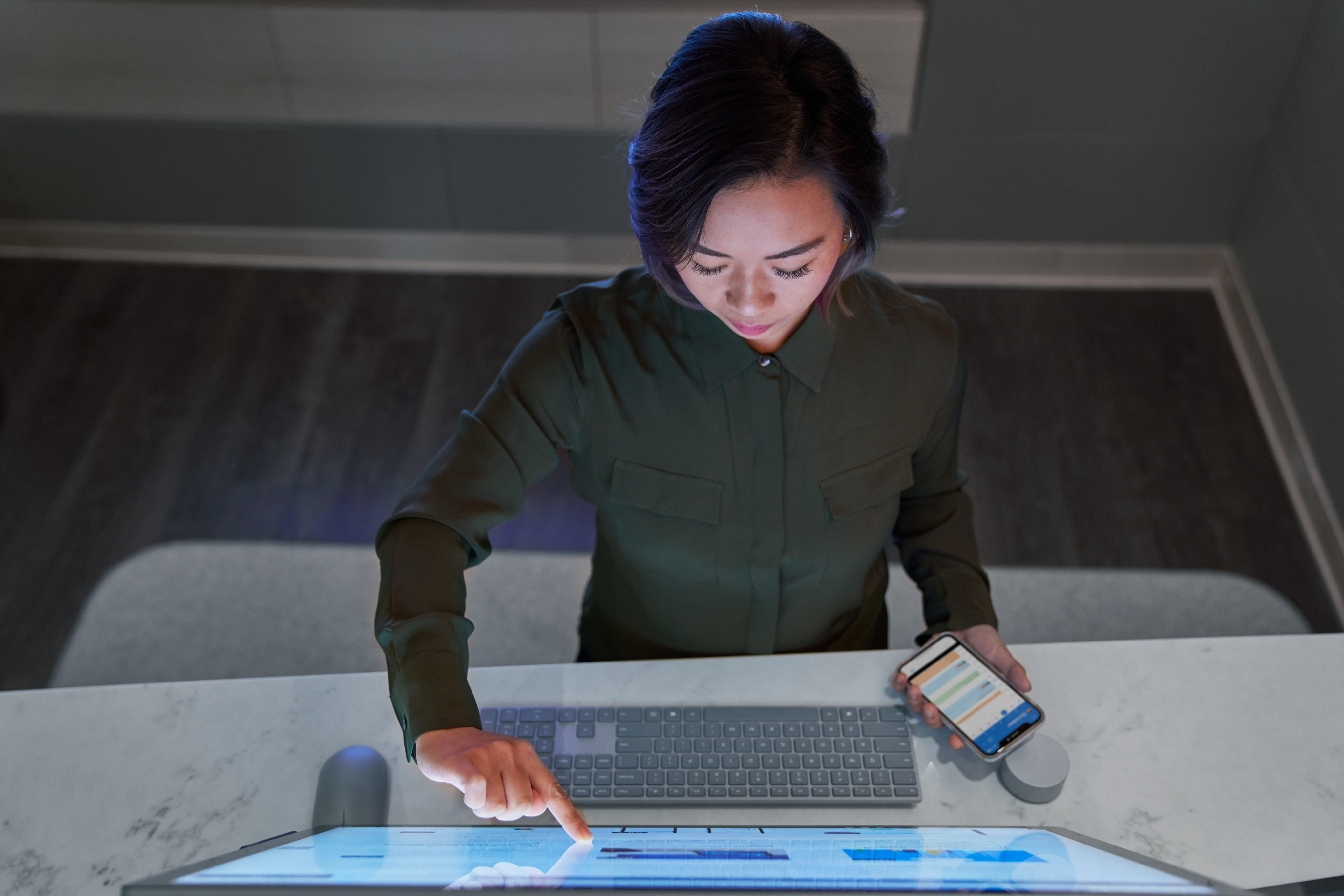 Top down view of a woman wearing a dark shirt in a dim office scrolling or working on a Microsoft Surface Studio and holding a phone.