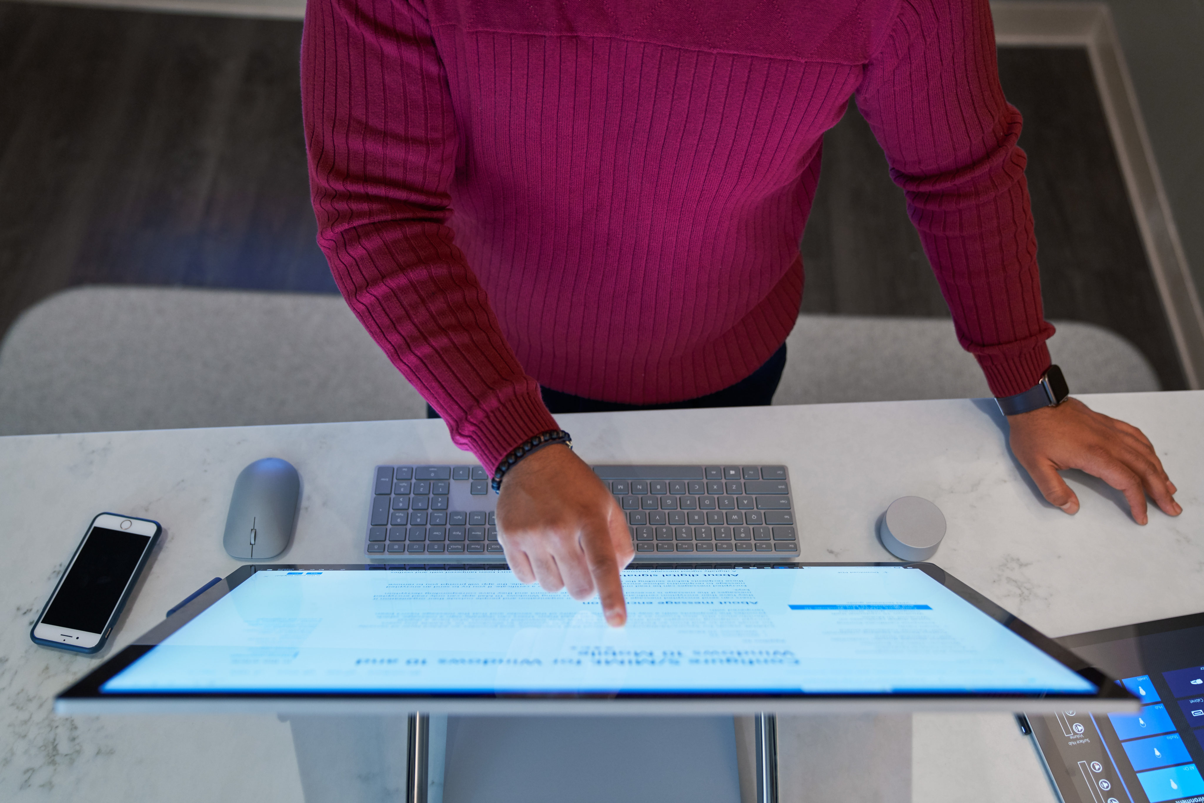 Top down view of a man wearing a dark red shirt working on a Microsoft Surface Studio with a phone next to him on the desktop along with a mouse, keyboard, and Surface Dial.