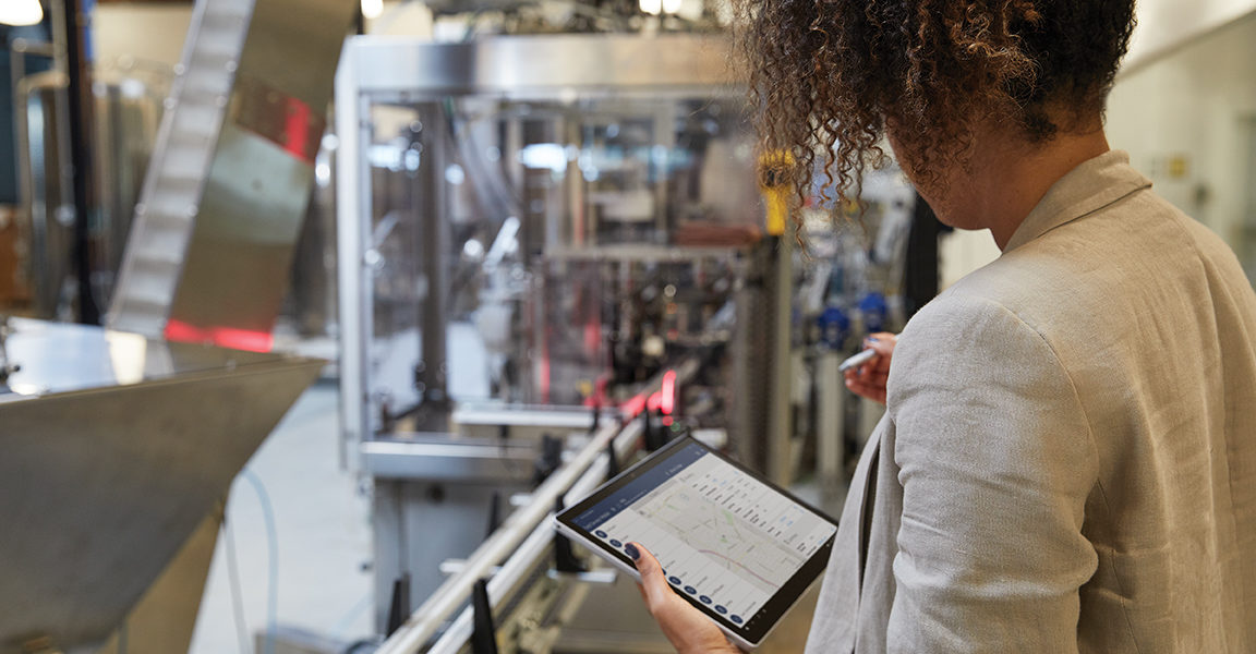 Adult female in an industrial factory setting holding a platinum Microsoft Surface Pro 7 in tablet mode while preparing to use a Microsoft Surface Pen with Microsoft Dynamics screen shown