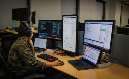 Black female developer wearing headphones; coding at her PC workspace in an enterprise office, using Visual Studio on a multi-monitor set up.