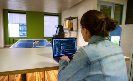 Female developer working on the go from the office breakroom or kitchen.