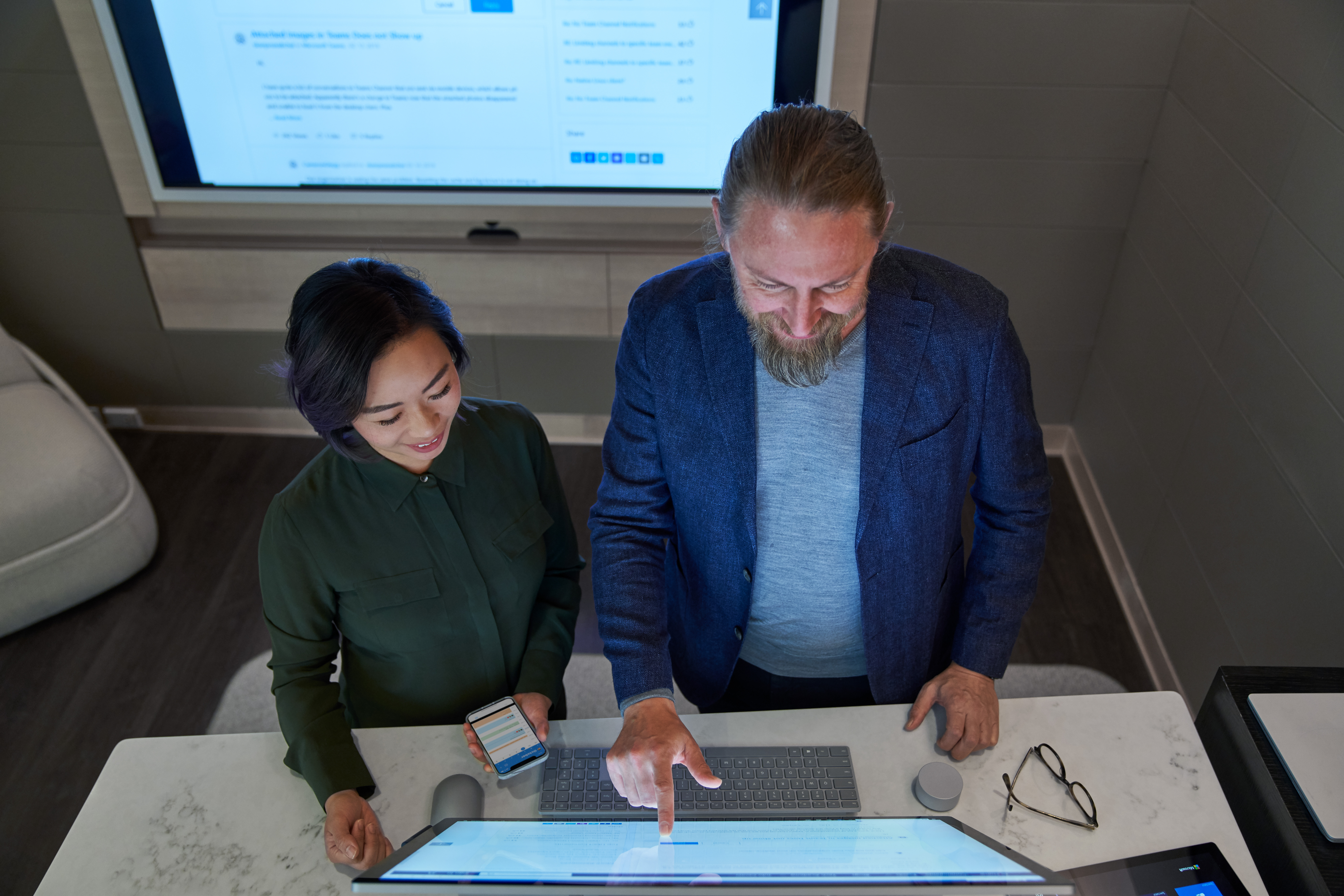 Top down view of a man and woman in a dim office collaborating or working on a Microsoft Surface Studio. She is holding a phone.