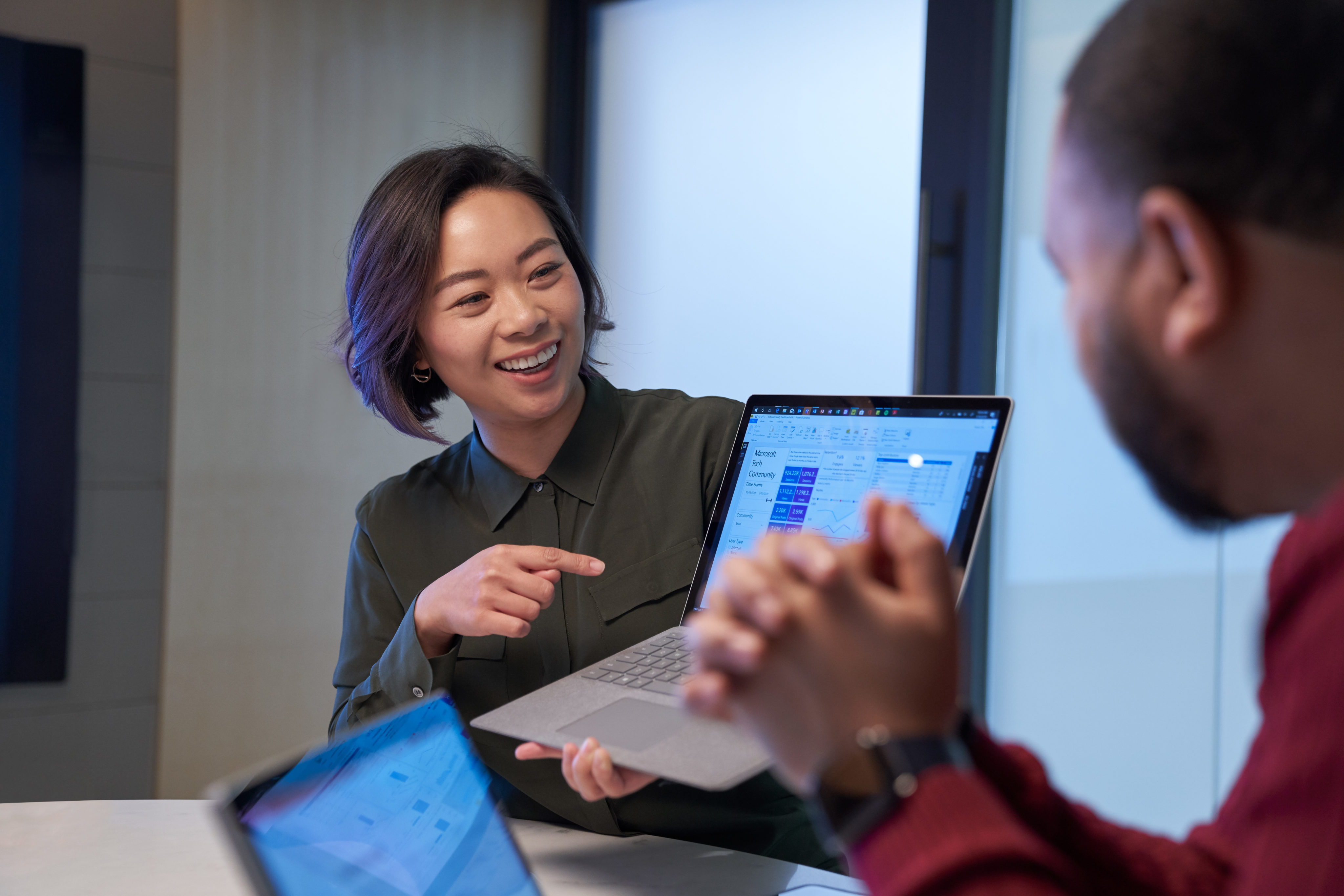Smiling woman in a meeting room holding up a Surface laptop presenting statistics. Blurred man in foreground.