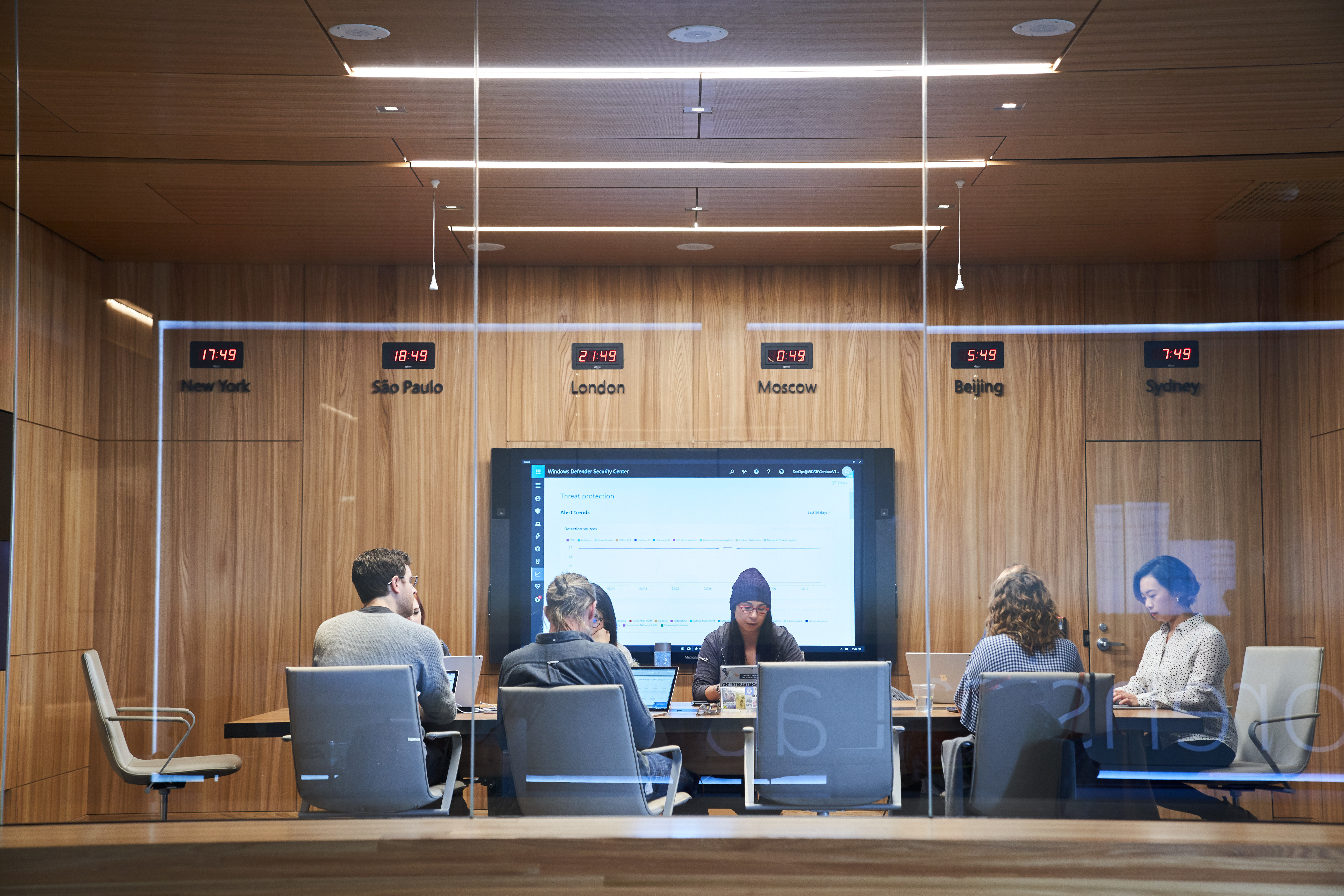 Looking into a conference room or board room meeting including people sitting around table in a room with international time clocks.