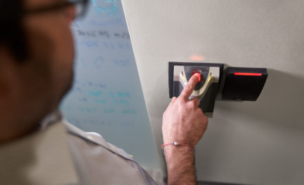 Man scanning his finger in a biometric fingerprint reader which will provide him access to a room.