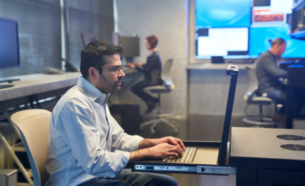 Man in a collared shirt working on a server station inside a secure room. Coworkers and large monitors are in the background. Keywords: network security, on-premise security, threat protection, secure score, monitoring, security management, operations, Microsoft Security collection