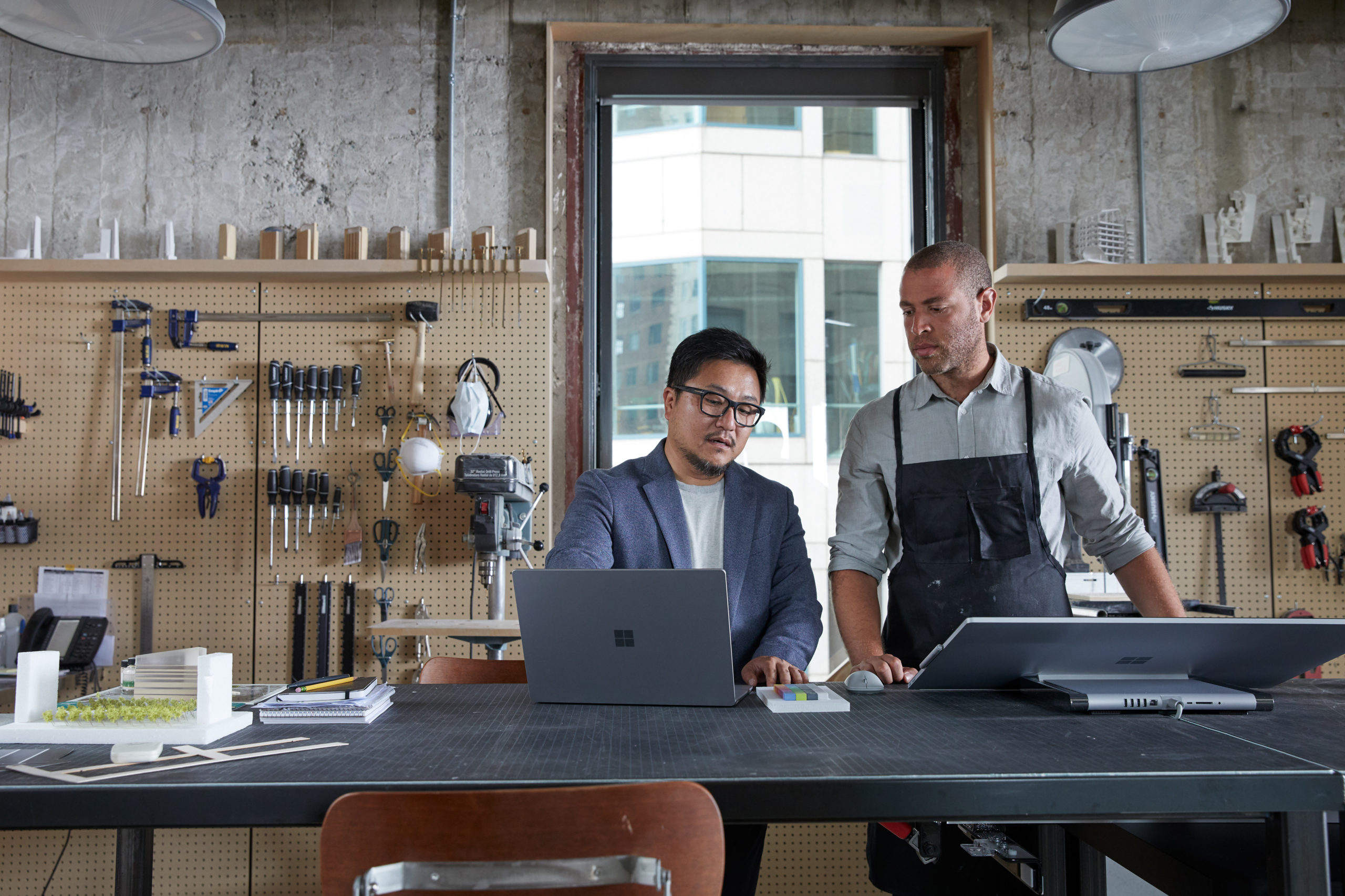 Two adult male collaborating in architecture modeling studio looking together on a platinum Microsoft Surface Laptop 3 and a platinum Microsoft Surface Studio 2.