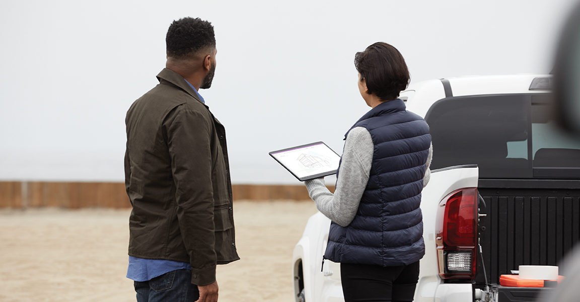 Two adults outside collaborating at a work site while using Microsoft OneNote. Female holding a black Microsoft Surface Pro X in tablet mode with male at her side.