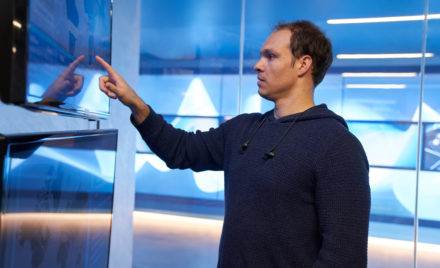 Man in a hooded sweater/sweatshirt inside a secure room, pointing at a geographic area displayed on a large monitor.