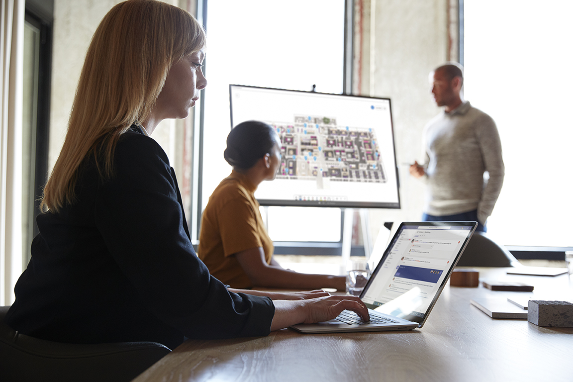"""Three adults are collaborating in a conference room. One male is standing next to a Microsoft Surface Hub 50"""" with Microsoft Whiteboard screen shown."""