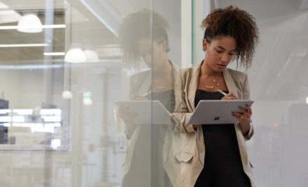 Adult female in industrial office setting leaning against a glass wall while holding a platinum Microsoft Surface Pro 7 in tablet mode preparing to write with Microsoft Surface Pen.