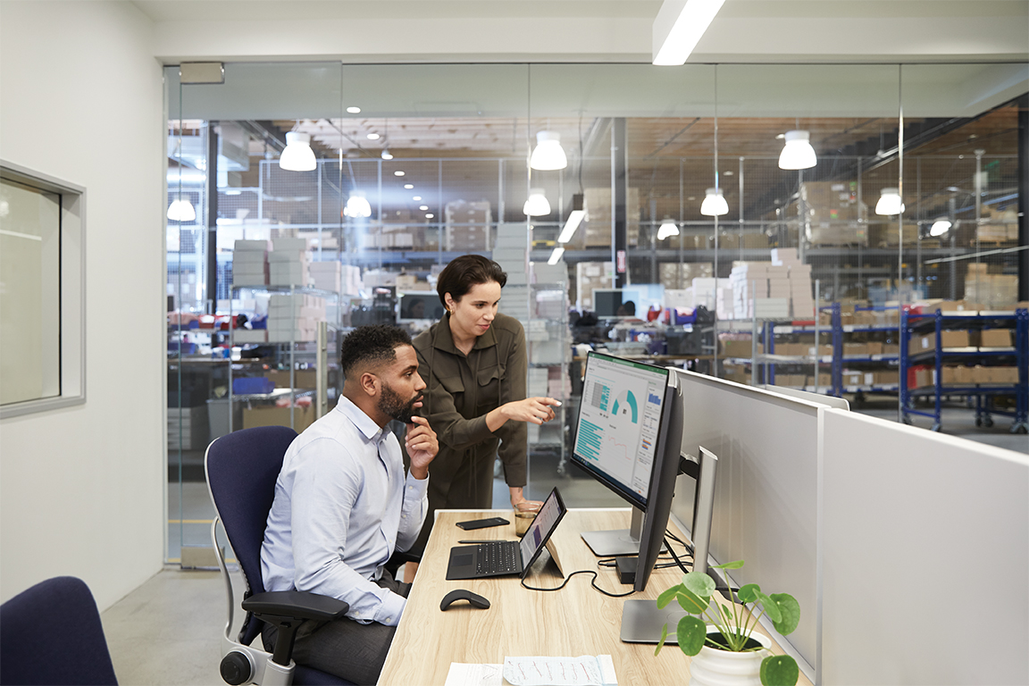 Two adults in an office adjacent to a warehouse setting collaborating while overlooking dual monitors.