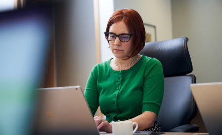 A red-haired woman with a green shirt and glasses, sitting inside an office working on her laptop.