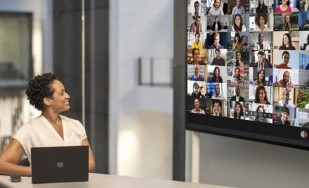 "Adult female meeting in a conference room while using Microsoft Teams Together Mode on a Surface Hub 2S 85"" device."