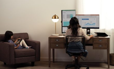 A mother and her daughter are working and learning remotely in their living room.