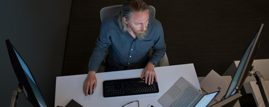 Top-down view of a bearded man in a gray/blue shirt seated at a desk working on a Surface laptop connected to three large monitors. Desktop has phone, glasses, mouse and other laptops on it.