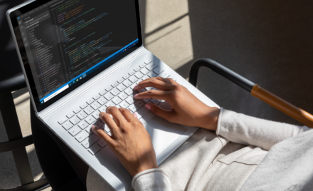 Commercial contextual lifestyle image of adult female working in Azure on Surface Book 3 inside.
