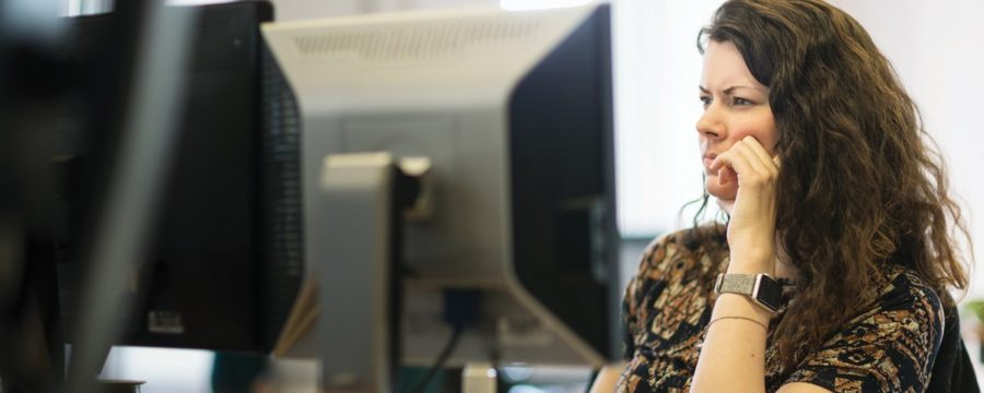 Adult woman sitting behind a computer screen.
