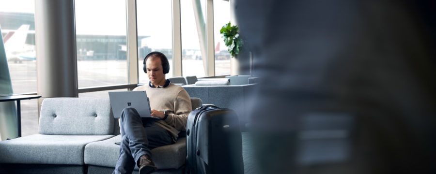 Adult male sitting in airport terminal working on his laptop.