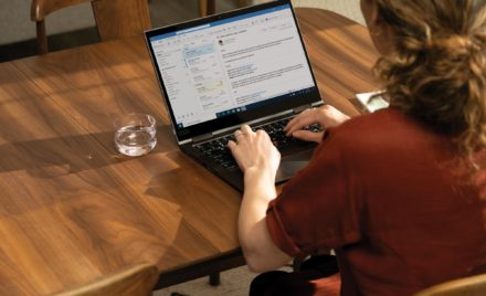 Over the shoulder photo of an adult woman at her dinning table looking at her Microsoft Outlook inbox.