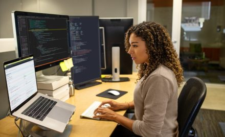 Black female developer working at enterprise office workspace. Focused work. She has customized her workspace with a multi-monitor set up.
