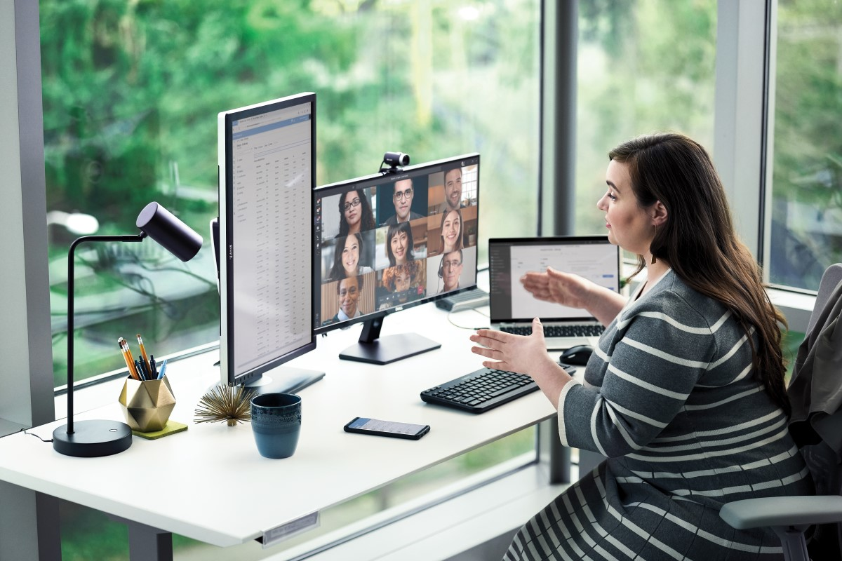Female enterprise employee working at desk with multiple devices, including HP Elitebook, running a Microsoft Teams conference call.