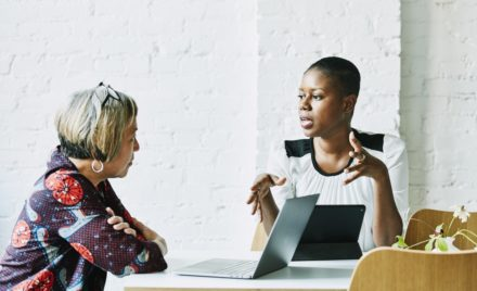 Female financial advisor in discussion with client in office conference room.