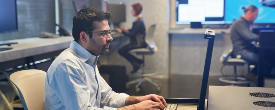Man in a collared shirt working on a server station inside a secure room. Coworkers and large monitors are in the background.