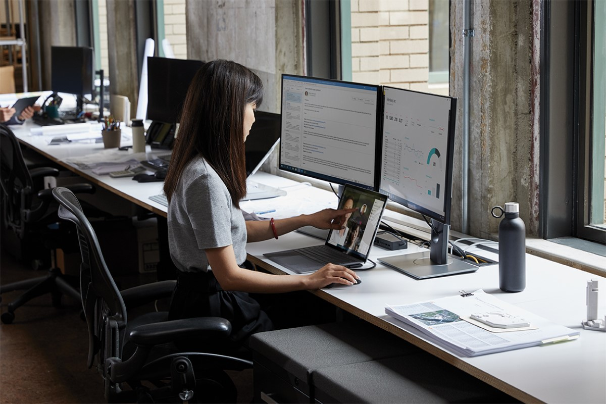 Adult female sitting at a desk in an office environment with a Microsoft Surface Laptop 3 using touchscreen to scroll.