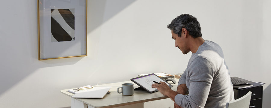 Adult male in home office environment using Microsoft OneNote at a desk with a black Microsoft Surface Pro 7 in studio mode. Black Microsoft Surface Pen in hand.