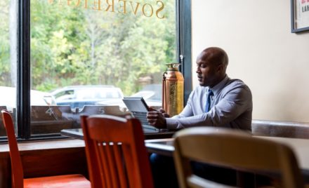 Male bank worker sitting in café restaurant using convertible laptop as tablet