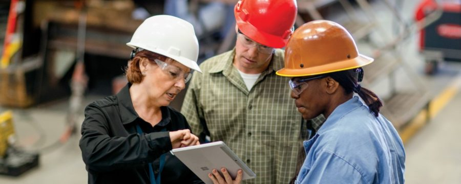 CEO of large manufacturing company discussing a project with operations manager and foreman.