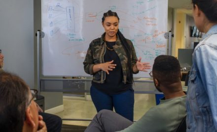 Real people, real offices. Black female developer speaking in front of a white board during team stand up meeting.