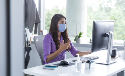 A female employee wearing a mask and talking on a video call with hand sanitizer on her desk, socially distancing from others.