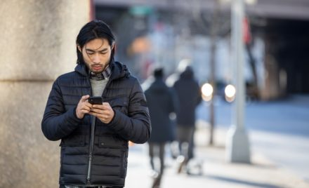 Small business male achieving outside the office (mobile) using a phone.