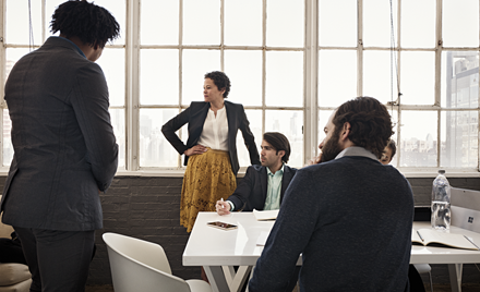 A group meets around a table in a meeting room.