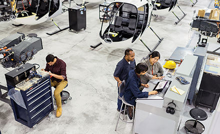 Image of workers assembling a helicopter. Several are gathered around a laptop.