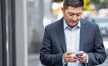 Image of a man checking his phone.
