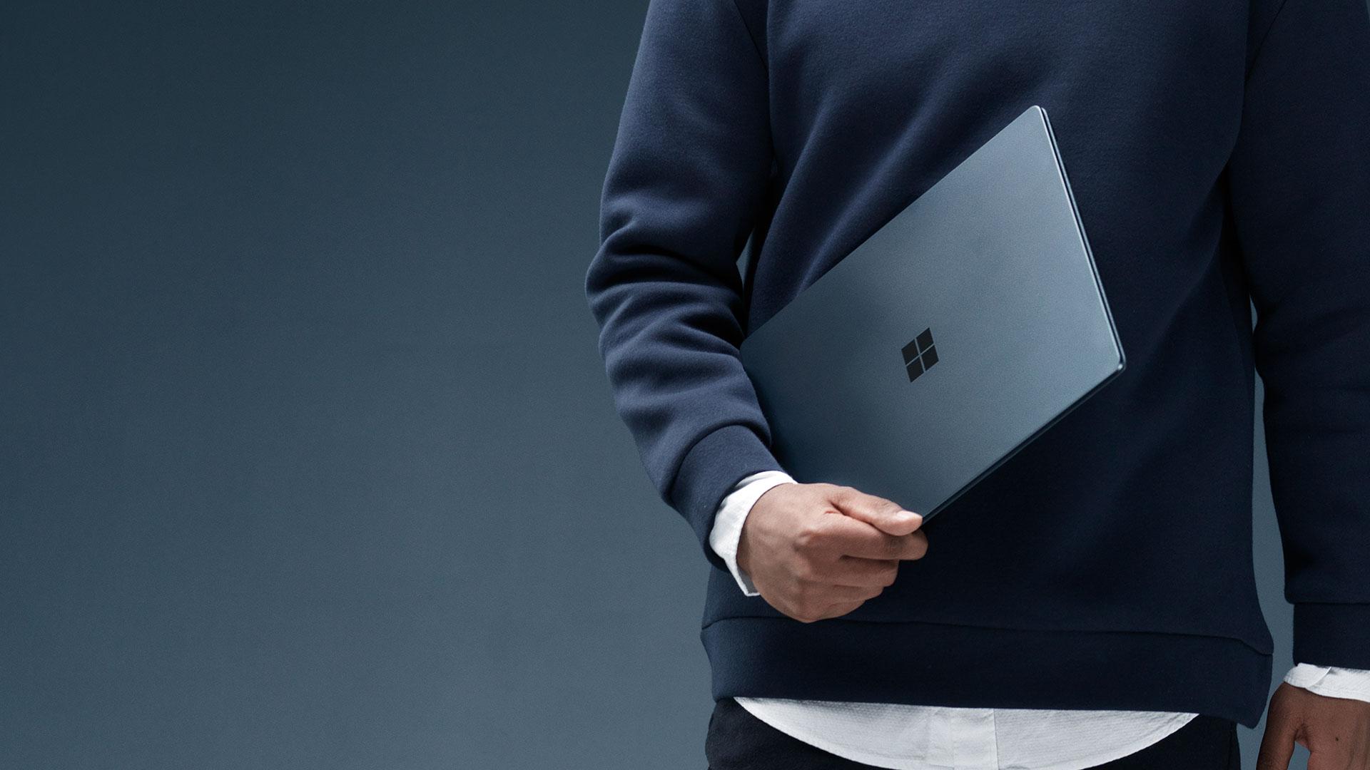 Man som håller en koboltblå Surface Laptop