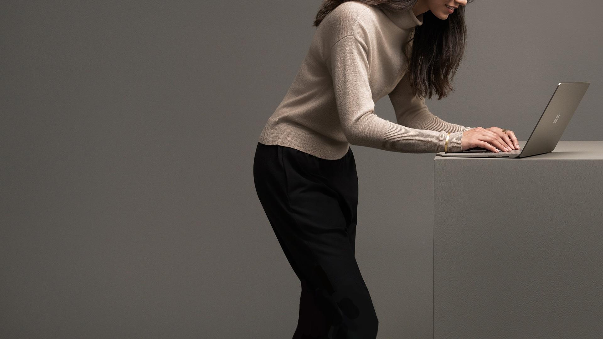 Kvinna som skriver på Surface Laptop i grafitguld.