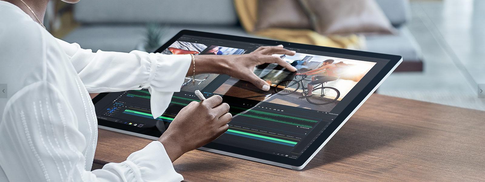 """En kvinna som använder Surface Studio """"pinch zooming"""" med penna och pekgester."""